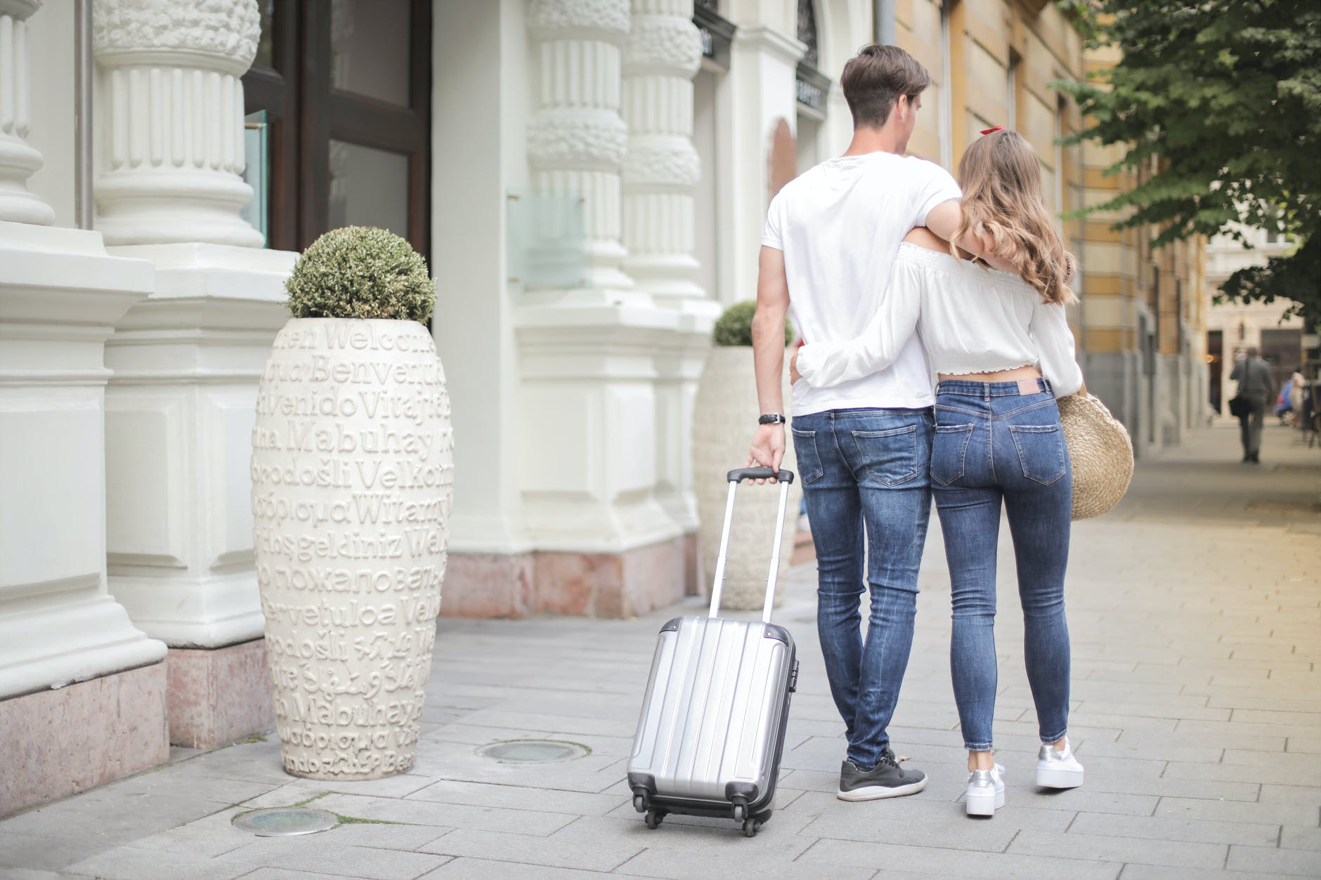 couple with suitcase walking along city street